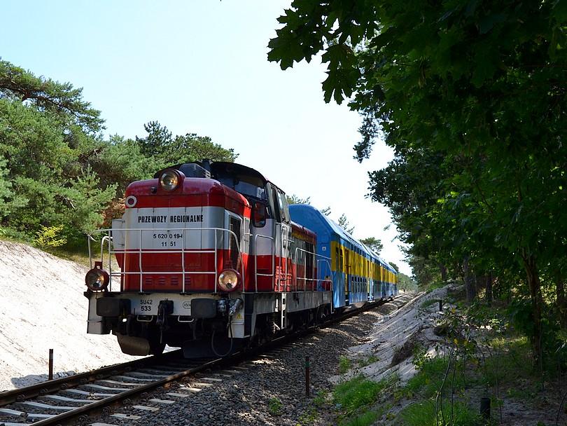 osobný vlak do Gdyne tvorený stonkou SU42-533 a starou poschodovou súpravou prechádza úsek medzi piesočnými dunami neďaleko výhybne Jastarnia, 17.7.2014