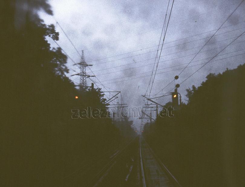 Návrat z depa Bratislava po údržbe do Zohoru. Daždivý tmavý deň roku 1982 nezabránil vyhotoviť fotografiu predzvestí a vchodových návestidiel do Lamača po aktivácii obojsmerného autobloku, zatiaľ po stanicu Zohor.