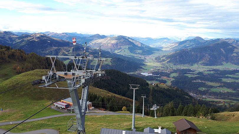 Stožiar č.30 gondolovej lanovej dráhy II na Kitzbühelerhorn. Naľavo vrchol Hahnenkamm (1712 m) so zjazdovkou svetového pohára v alpskom lyžovaní. V údolí jazero Schwarzsee a železničná trať do Innsbrucku