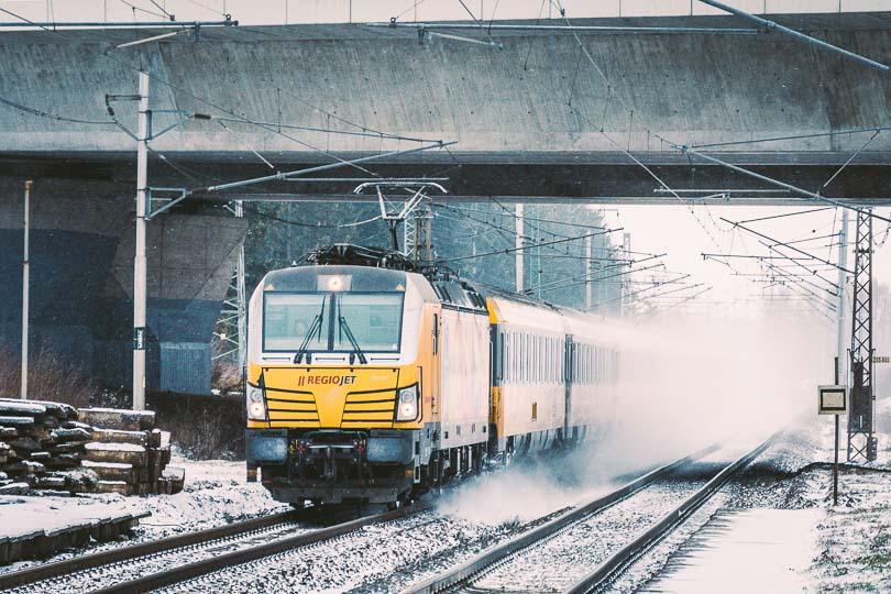 Popod diaľničný nadjazd prechádza žltý Vectron s vlakom RJ 1003.