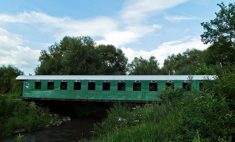 Bočný pohľad na vagón. Ešte je potrebné vykosiť trávu, ktorú bude treba kosiť aj potom naďalej. Koryto rieky pod vagónom je veľké a rieka je kľudná.