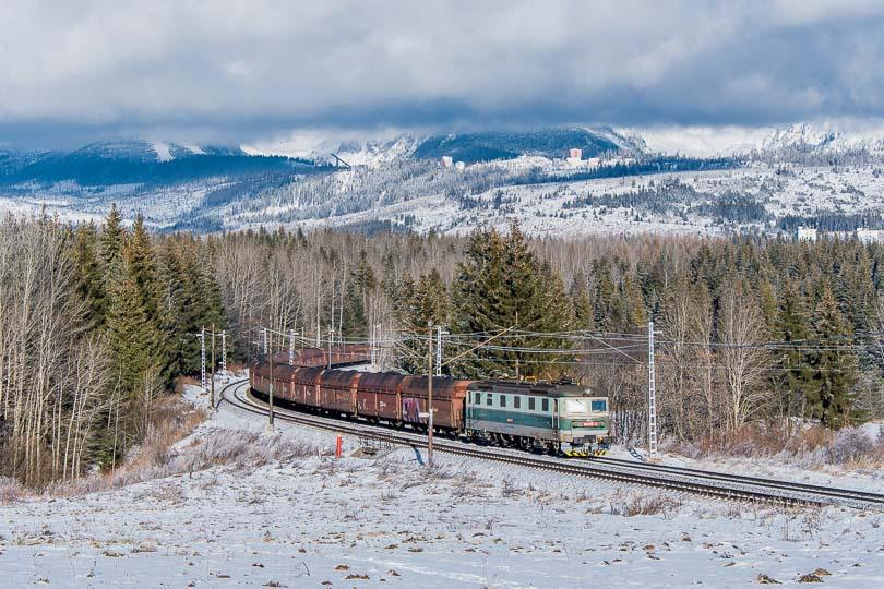 Medzičasom prišli zo západu oblaky a pred Tatry padla opona, ale stále ostalo slnečno. Rušeň 183 025 na postrku nákladného vlaku.