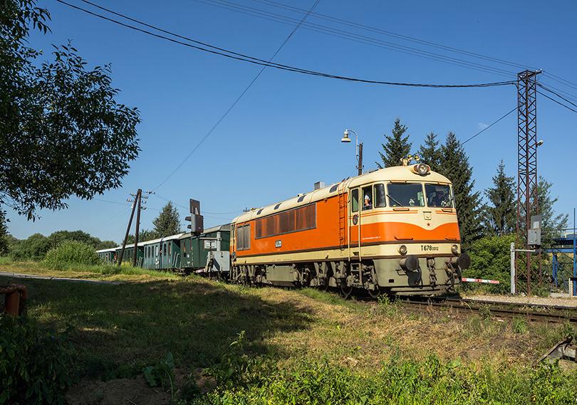 T 678.012 prechádza svojim vlakom cez stanicu a následné priecestie.(Foto:Duko)