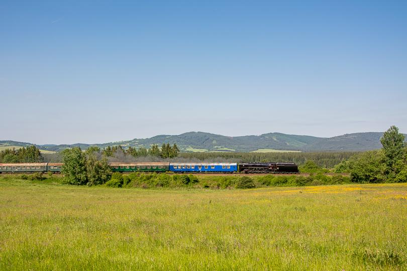 Vlak odchádza zo stanice Horná Štubňa. Vlak je zachytený na neďalekej lúke.