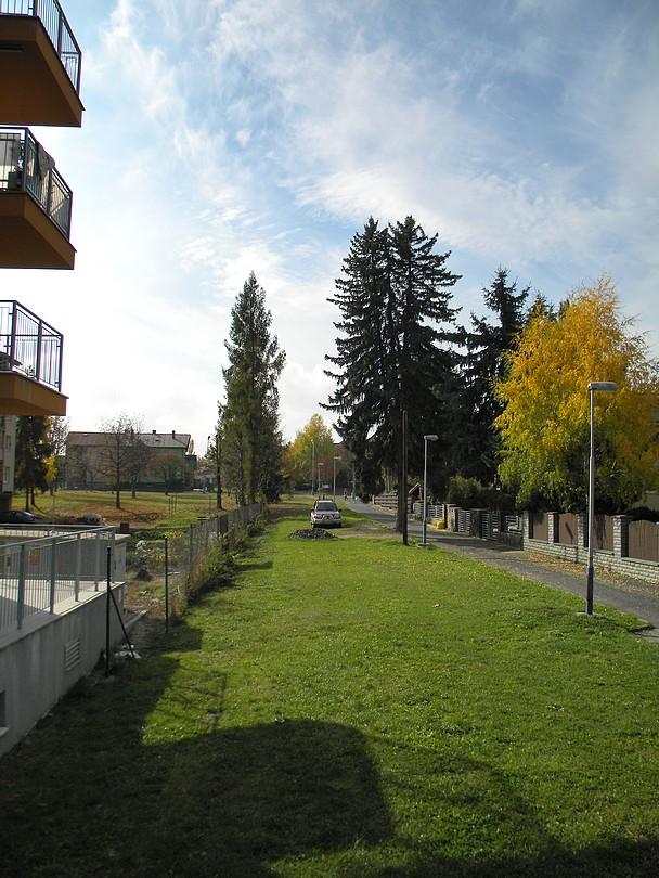 Šírka trávnika odhaľuje, že tu pôvodne išla dráha ( Pohľad od námestia ).
