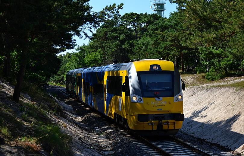 osobný vlak do stanice Hel tvorený motorovou jednotkou SA137-001 a cyklovozňom míňa piesočné duny neďaleko výhybne Jastarnia, 17.7.2014